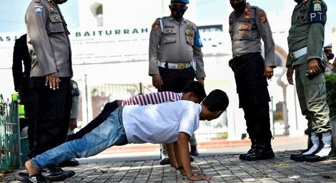 Observados por policiais, flagrados sem máscara fazem flexões em Banda Aceh