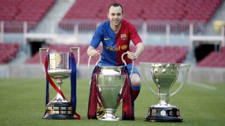 Iniesta, com os troféus da Copa, Liga e Champions da temporada 2008/09