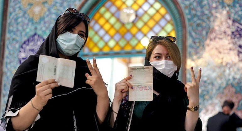 Eleitoras mostram documento de identificação com os carimbos da eleição presidencial no Irã