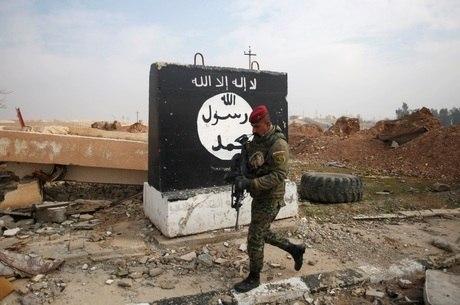 Soldado iraquiano passa em frente a bandeira do Daesh