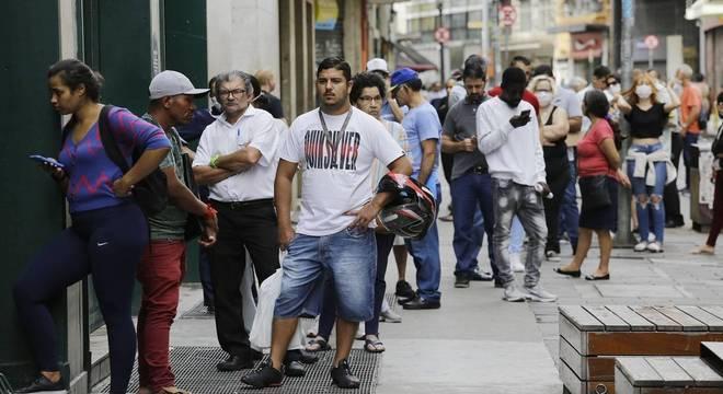 Fila de pessoas em frente a uma agência bancária na região central de São Paulo