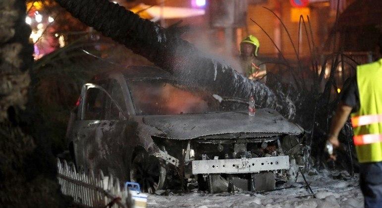 Bombeiros apagam incêndio em carro atingido por foguete em Holon, perto de Tel Aviv
