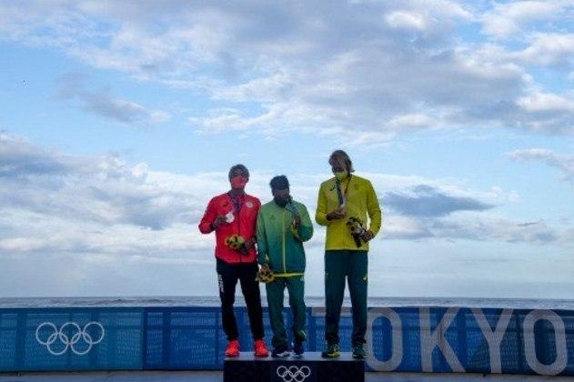 Ítalo Ferreira posa feliz com sua medalha de ouro no surfe olímpico.