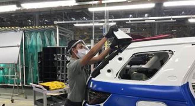 Colaborador da Jaguar Land Rover usando novos EPIs na linha de produção
