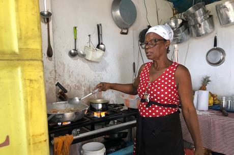 Janice cozinha em seu quiosque, onde o movimento caiu 80%