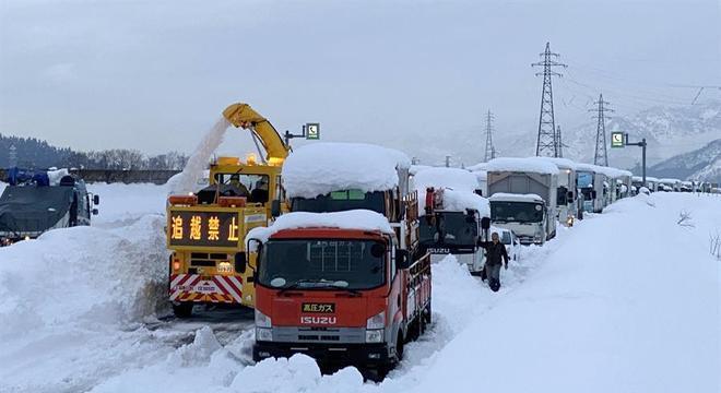 Com escavadeiras, operários tentaram limpar a estrada coberta de neve