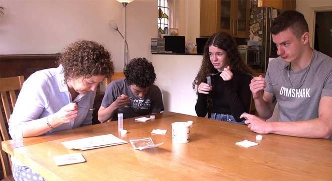 Jayne e seus três filhos adolescentes, Sam, Meg e Billy, cuspindo em uma colher para realizar teste de coronavírus