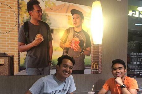 Jevh e Christian ao lado do pôster que produziram e penduraram no McDonald's: 'Não havia asiáticos' nas peças publicitárias, diz ele