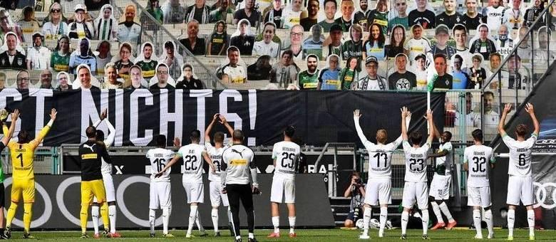 Jogadores do Borussia Mönchengladbach saudam imagens de torcedores em papelão colocadas no estádio
