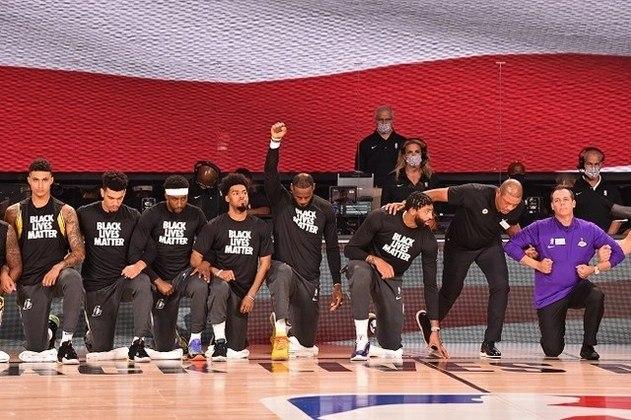 Jogadores do Los Angeles Lakers ajoelham-se minutos antes de entrarem em quadra diante do Los Angeles Clippers, prestando homenagem durante o hino dos EUA em apoio ao movimento Black Lives Matter (Vidas Negras Importam), na luta contra a brutalidade racial e injustiça social