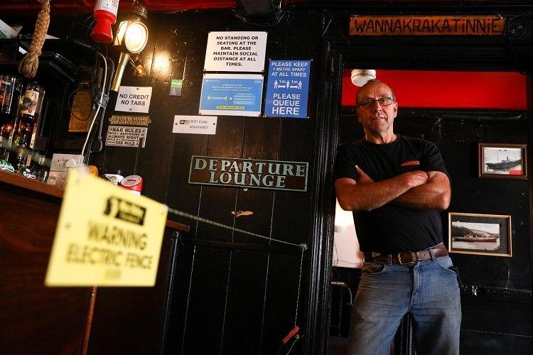 O dono do pub Star Inn posa ao lado de cerca elétrica