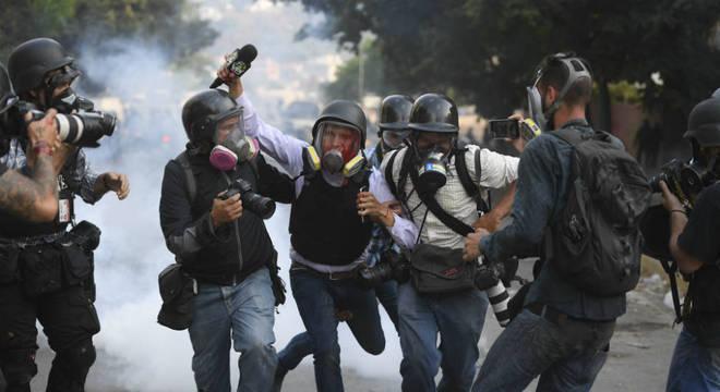 Jornalista ferido é ajudado por colegas durante protesto nas ruas da Venezuela