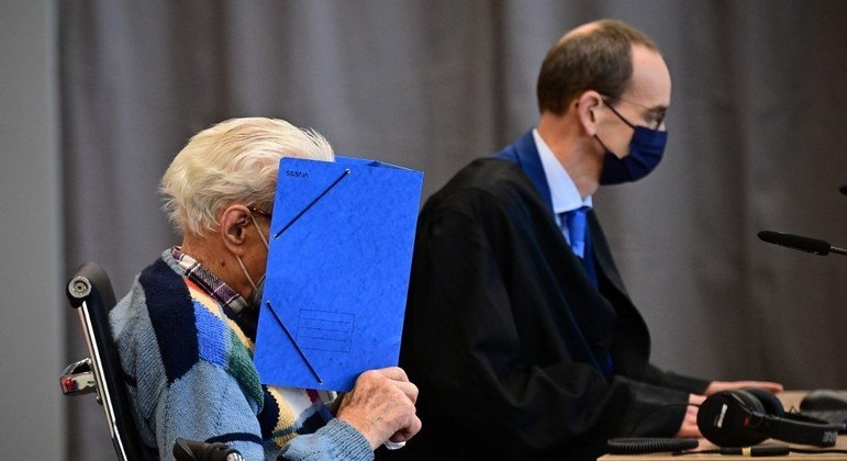 O réu Josef Schutz senta-se ao lado de seu advogado Stefan Waterkamp e esconde seu rosto atrás de uma pasta