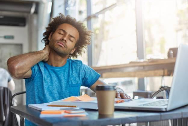Jovem negro sentado em frente ao notebook coma as mãos na nuca e olhos fechados