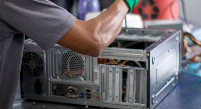 Jovem conserta computadores que serão encaminhados para doação