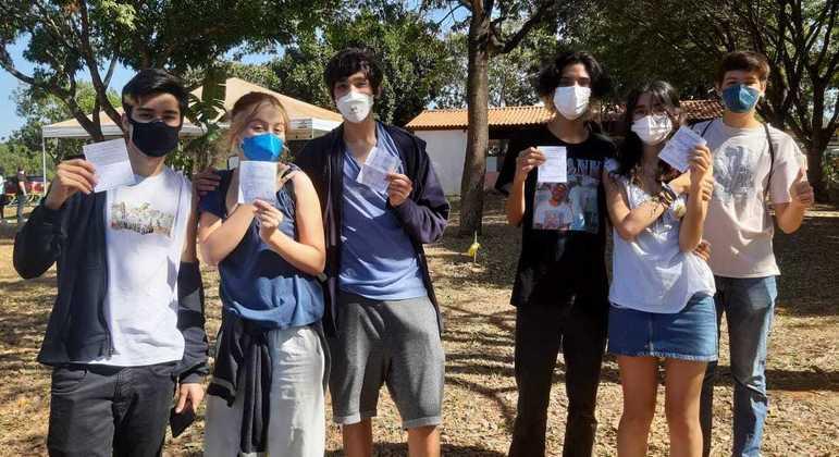 Adolescentes exibem cartões de vacinação após receberem imunização no DF