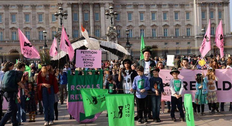 Jovens em frente ao Palácio de Buckingham cobram a família real sobre o meio ambiente