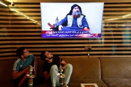 Jovens iraquianos observam o momento do anúncio da morte do líder terrorista