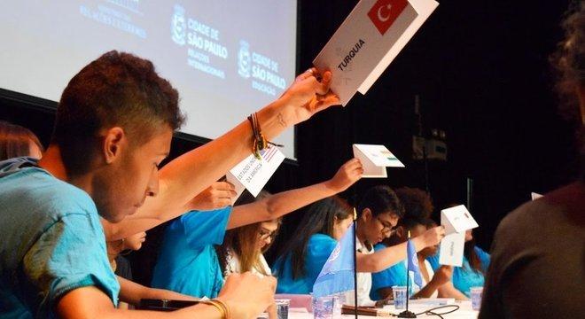 Jovens erguem os cartazes de 'seus' países para sinalizar que querem se manifestar