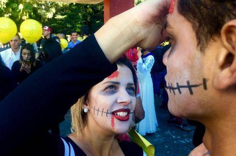Jovem aplica maquiagem de zumbi em participante