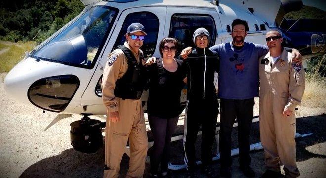 Krystal Ramirez (à esquerda), Hunter Whitson (ao centro) e Curtis Whitson (à direita) posam para foto com equipe de resgate