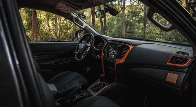 Interior tem um aplique central e nas molduras de ar além de um emblema na cor laranja