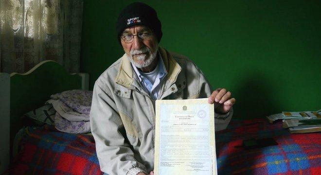 Leonardo da Cruz, pai de Robson, mostra a certidão de óbito do filho, ainda com a inscrição 'desaparecido'