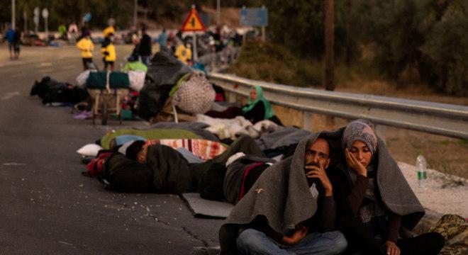 Imigrantes e refugiados se abrigam em acostamento após incêndio na ilha grega de Lesbos