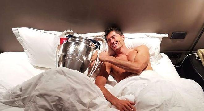 Lewandowski deitado com o troféu da Champions. O de melhor do mundo chegará