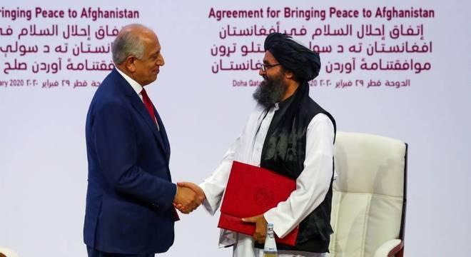 Zalmay Khalilzad da delegação dos EUA e o líder talibã, Mullah Abdul Ghani Baradar