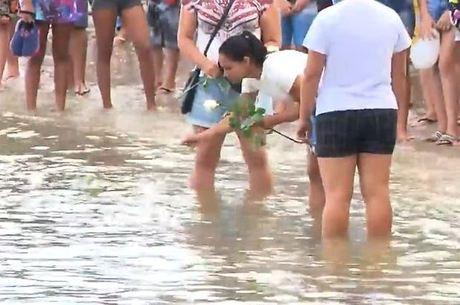 Mãe de Benjamim joga flores ao mar