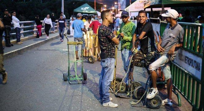 Muitos venezuelanos cruzam a fronteira durante o dia, para ganhar dinheiro fazendo bicos, e retornam de noite ao país. Esse grupo de jovens ganha trocados carregando as malas de quem cruza a ponte