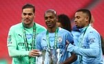 Brasileiros Ederson, Fernandinho e Gabriel Jesus posam com o troféu da Copa da Liga Inglesa, conquistado pelo Manchester City neste domingo (25) após vitória por 1 a 0 sobre o Tottenham, em Wembley. O clube chegou ao tetracampeonato consecutivo e à oitava conquista na competição em sua história