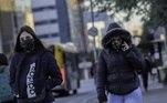 Duas mulheres usando casacos e máscaras de proteção caminham em viaduto