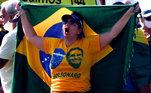 Manifestante com bandeira do Brasil e camiseta com a imagem do presidente Jair Bolsonaro em ato na praia de Copacabana