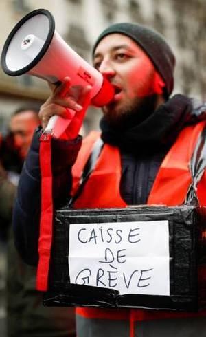 Manifestante segura caixa de doações de recursos para greve durante protesto em Paris