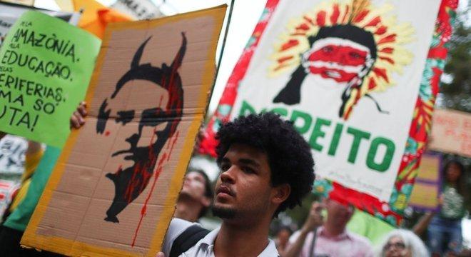 Manifestante no Rio de Janeiro exibe cartaz satirizando Bolsonaro; pauta ambiental deverá estar no discurso do presidente brasileiro na ONU