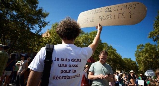 Manifestante protesta a favor do decrescimento na França em 2018, com cartaz em que se lê: 'Crescimento ou clima, o que é prioridade?'