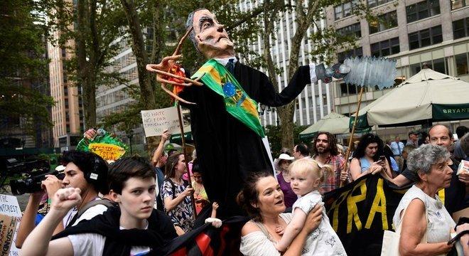 Manifestantes carregam marionete satirizando Bolsonaro em Nova York; presença do presidente brasileiro na cidade americana foi motivo de protestos contra a sua política ambiental