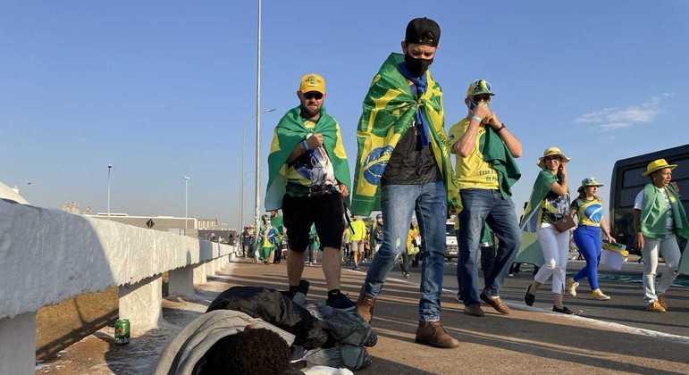 Manifestantes pró-Bolsonaro chegam à Esplanada dos Ministériose observam homem deitado no chão