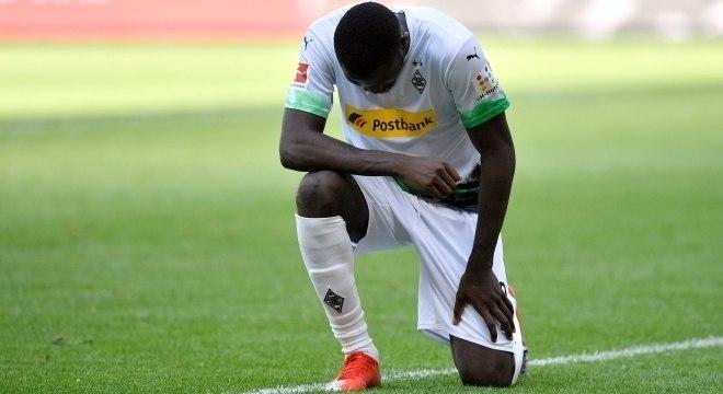 Atacante Marcus Thuram se ajoelha após  gol do Moenchengladbach