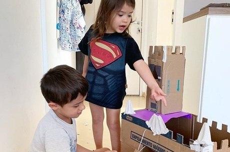 Theo e Anna brincam com castelo de papelão