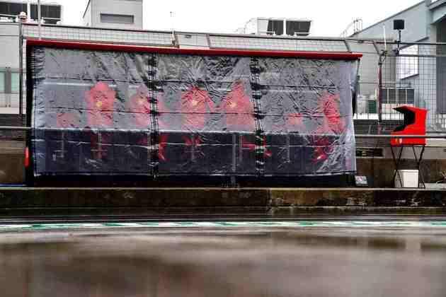 Membros do pit-wall da Ferrari se protegeram da chuva na Alemanha