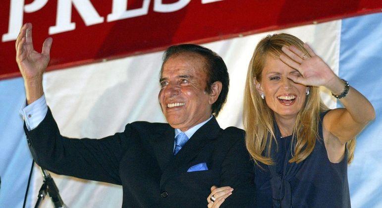 Carlos Menem acena com sua mulher Cecilia Bolocco durante campanha presidencial