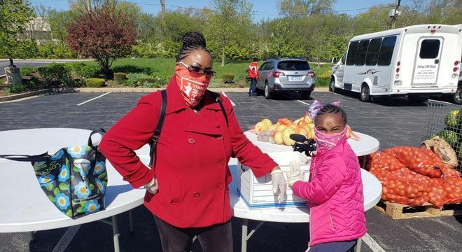 Olivia e sua mãe, Linda Tyler, num estacionamento fazendo as doações