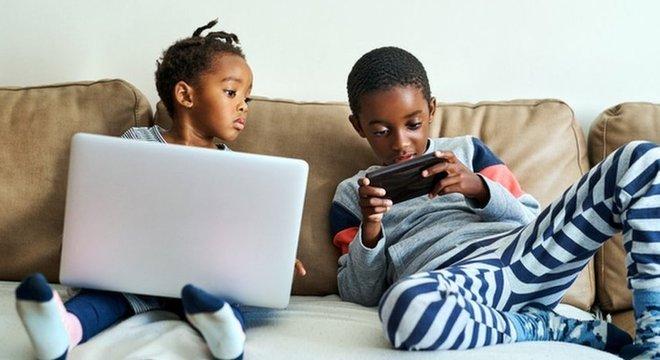 Menina e irmão usam computador e celular no sofá