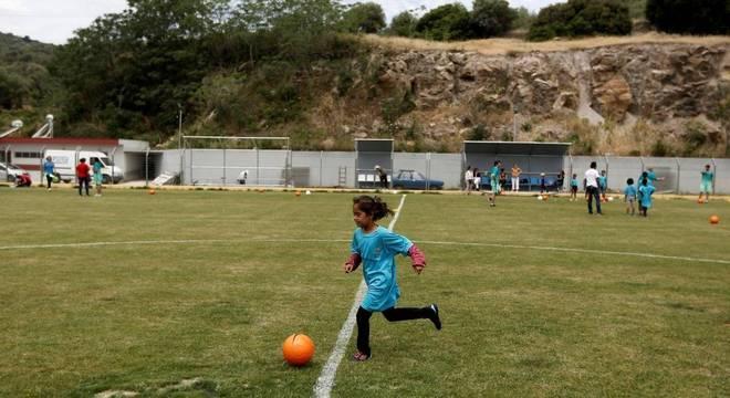 Menina joga futebol na ilha de Lesbos, na Grécia