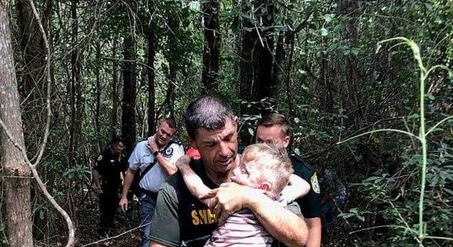 Menino autista sendo salvo pelo policial após desaparecer