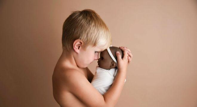 Menino com sua boneca preferida no ensaio newborn