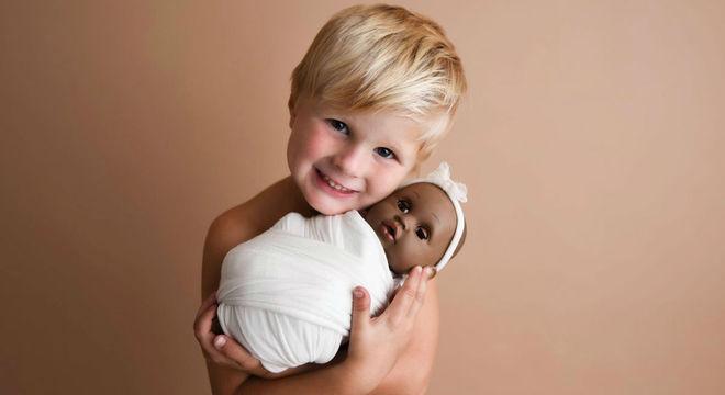 Menino no ensaio newborn com a boneca preferida